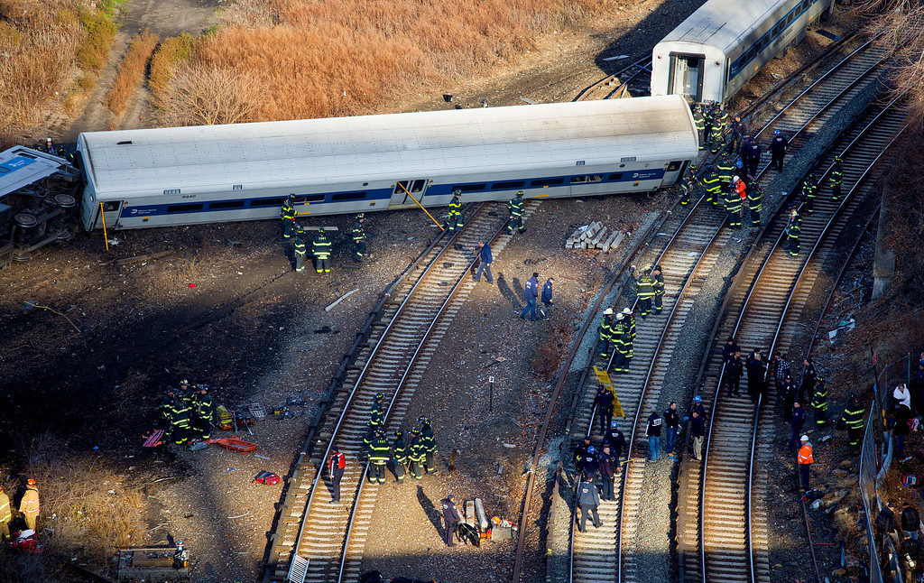. First responders gather at the derailment of a Metro-North passenger train in the Bronx borough of New York Sunday, Dec. 1, 2013. The train derailed on a curved section of track in the Bronx on Sunday morning, coming to rest just inches from the water and causing multiple fatalities and dozens of injuries, authorities said. Metropolitan Transportation Authority police say the train derailed near the Spuyten Duyvil station. (AP Photo/Craig Ruttle)