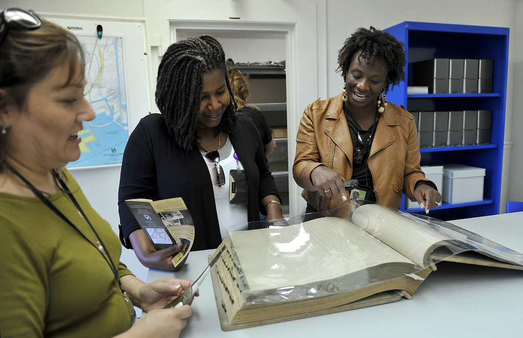 . 4/11/13 - L-R Debra Espinoza, Kendra Cantrell, and Renee Jones, port of LA employees in the engineering division look through a payroll book from 1913 as they toured the new office in Wilmington, housing the priceless history of the port and harbor area. The facility will be open by appointment only and able to help with research. Geraldine Knatz, Port Executive Director, is a history buff and has been the driving force behind the archive project. Photo by Brittany Murray / Staff Photographer