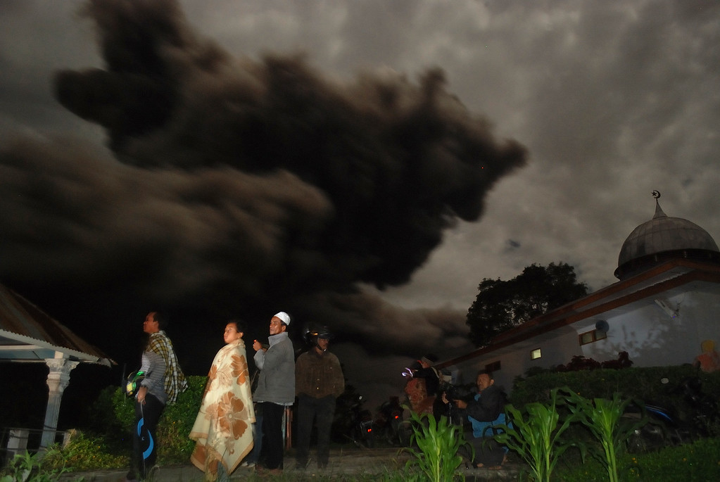 . Residents gather outside their houses in Karo district as dark giant ash clouds, seen in the background, rise from the crater of Mount Sinabung volcano during an eruption late October 7, 2014 following an earlier eruption on October 5, 2014. AFP PHOTO / SUTANTA  ADITYA/AFP/Getty Images