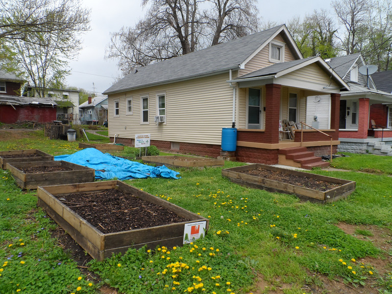 The Boston Court Community Garden outside a completed Save a House/Make a Home project.