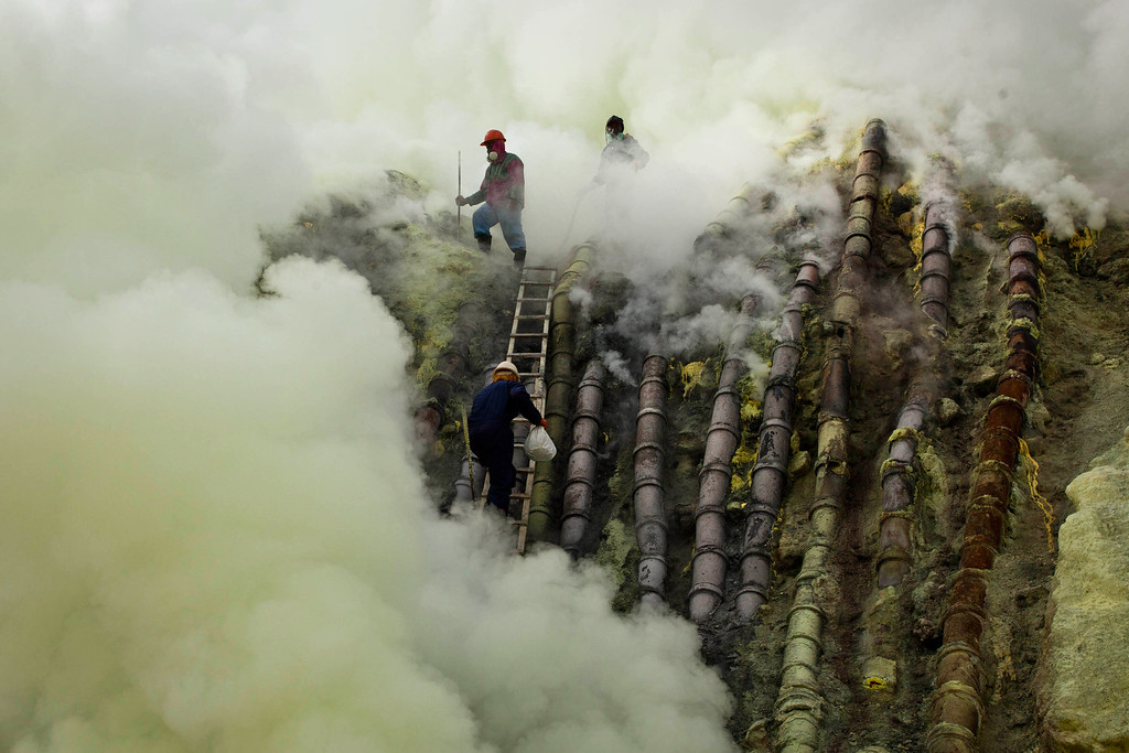 . A sulfur miner carries a goats head in a white bag as he climbs to bury the head in the crater as part of an annual offering ceremony on the Ijen volcano on December 17, 2013 in Yogyakarta, Indonesia.  (Photo by Ulet Ifansasti/Getty Images)