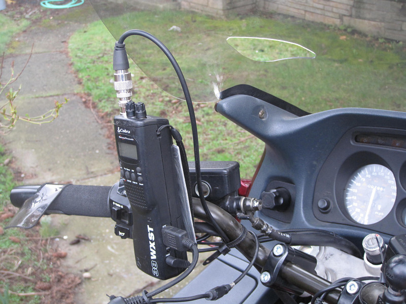 """COBRA radio on custom mount plate which is affixed to the clutch mounting bolts.  Normally the lanyard is wrapped around the mount plate as an additional security strap.  The sound is piped into my helmet using the cable in the foreground.  Note that my bike has 2"""" risers (which I really, really like)."""