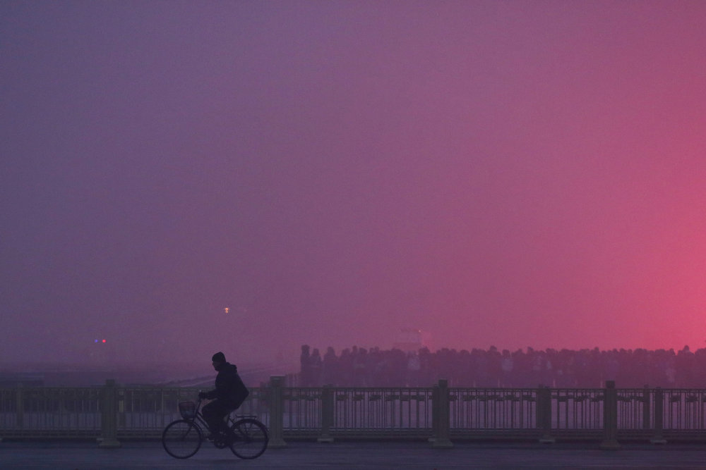 Description of . A men rides a bicycle as tourists waiting the flag-raising ceremony during severe pollution at Tiananmen Square on January 29, 2013 in Beijing, China. The 4th dense fog envelops Beijing with pollution at hazardous levels in January.  (Photo by Feng Li/Getty Images)