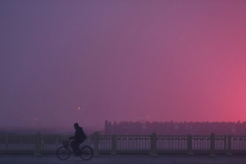. A men rides a bicycle as tourists waiting the flag-raising ceremony during severe pollution at Tiananmen Square on January 29, 2013 in Beijing, China. The 4th dense fog envelops Beijing with pollution at hazardous levels in January.  (Photo by Feng Li/Getty Images)