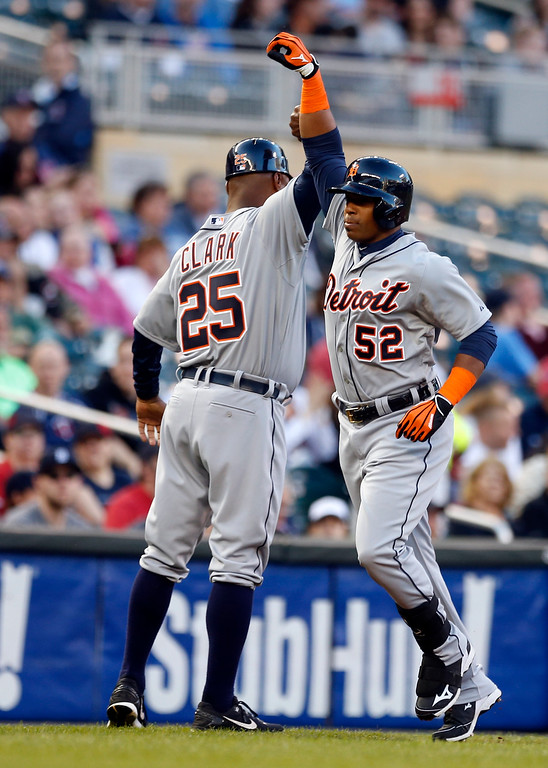 . Detroit Tigers� Yoenis Cespedes, right, and third base coach Dave Clark celebrate Cespedes\' three-run home run off Minnesota Twins pitcher Tommy Milone in the first inning of a baseball game, Monday, April 27, 2015, in Minneapolis. (AP Photo/Jim Mone)
