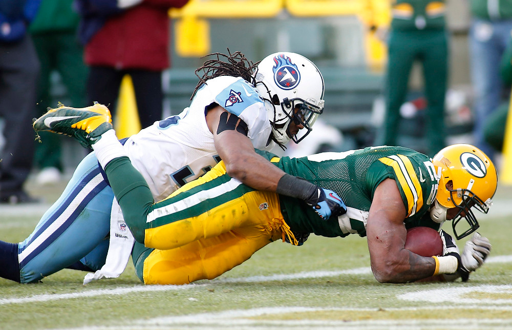. Green Bay Packers running back Ryan Grant scores a touchdown against Tennessee Titans safety Michael Griffin (L) during the second half of a NFL football game in Green Bay, Wisconsin December 23, 2012. Packers defeated the Titans 55-7. REUTERS/Darren Hauck