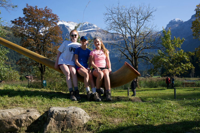 Merritt, Marin, and Mady sitting atop an alpenhorn statue just outside of Lenk