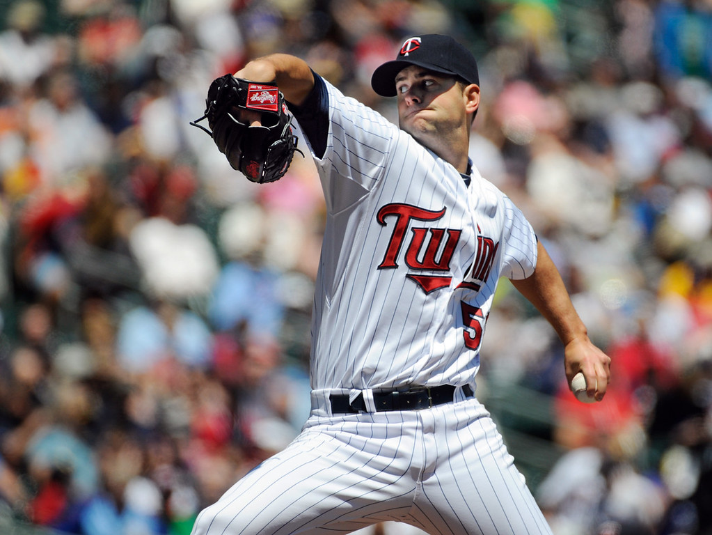 . Twins starter Scott Diamond pitches against the Mariners during the first inning. Diamond spread four hits over six scoreless inning to earn his fourth win of the season.  (AP Photo/Craig Lassig)