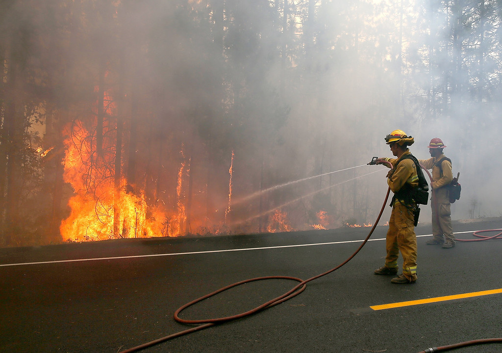 . GROVELAND, CA - AUGUST 22:  Firefighters douse hot spots while battling the Rim Fire on August 22, 2013 in Groveland, California. The Rim Fire continues to burn out of control and threatens 2,500 homes outside of Yosemite National Park. Over 1,000 firefighters are battling the blaze that was reduced to only 2 percent containment after it nearly tripled in size overnight.  (Photo by Justin Sullivan/Getty Images)