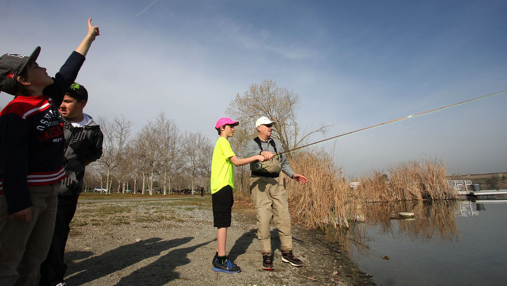 . Brady Willis, 13, of Tracy, gets a fly fishing lesson from Patrick Ferguson, a member of Tracy Fly Fishers, as part of the Trout in the Classroom program sponsored by the State Department of Fish and Wildlife at Shadow Cliffs Regional Recreation Area in Pleasanton, Calif., on Thursday, March 14. Classes are given 35 trout eggs and tanks. When the hatchlings are large enough they are released into local lakes.  About 200 students and teachers released fish at Shadow Cliffs.  (Jim Stevens/Staff)