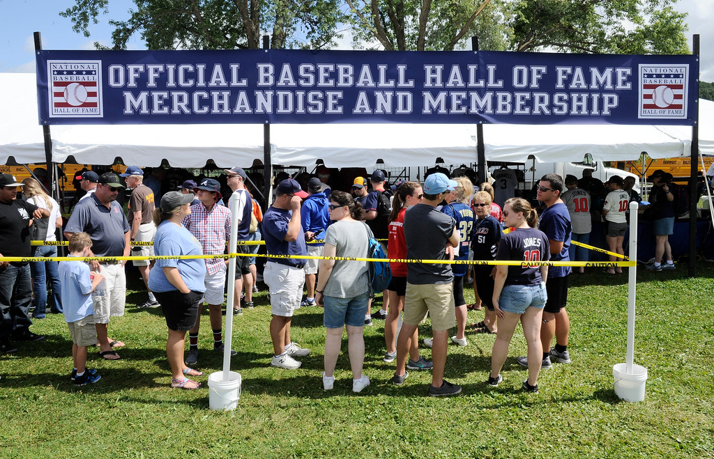 . Fans buy baseball merchandise before the start of National Baseball Hall of Fame induction ceremonies Sunday, July 29, 2018, in Cooperstown, N.Y. (AP Photo/Hans Pennink)