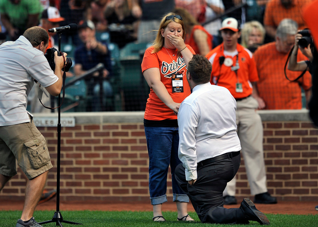 . Singer Michael Fries proposes to Shelby Trautman after singing the national anthem before the Baltimore Orioles against the Colorado Rockies baseball game on Saturday, Aug. 17, 2013, in Baltimore.(AP Photo/Gail Burton)