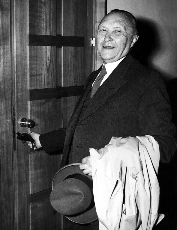 . 1953: Konrad Adenauer. West German Chancellor Konrad Adenauer smilingly unlocks his office door as he resumes his daily work on Sept. 7, 1953 in Bonn, Germany after his sweeping victory in the West German parliamentary election. (AP Photo/Albert Gillhausen)