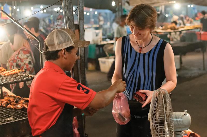 Helga kauft bei einem Händler ein wenig gegrillten Rochen.