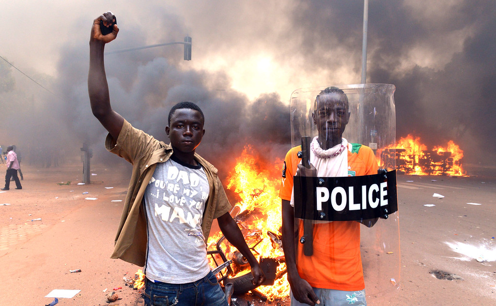 . Protesters pose with a police shield outside the parliament in Ouagadougou on October 30, 2014 as cars and documents burn outside. Hundreds of angry demonstrators in Burkina Faso stormed parliament on October 30 before setting it on fire in protest at plans to change the constitution to allow President Blaise Compaore to extend his 27-year rule. Police had fired tear gas on protesters to try to prevent them from moving in on the National Assembly building ahead of a vote on the controversial legislation. But about 1,500 people managed to break through the security cordon and were ransacking parliament.    AFP PHOTO / ISSOUF  SANOGO/AFP/Getty Images