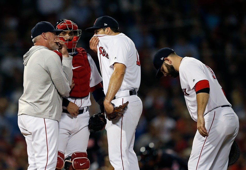 . Boston Red Sox pitching coach Dana LeVangie, left, talks with Nathan Eovaldi, center, during the fourth inning of a baseball game against the Cleveland Indians in Boston, Tuesday, Aug. 21, 2018. (AP Photo/Michael Dwyer)