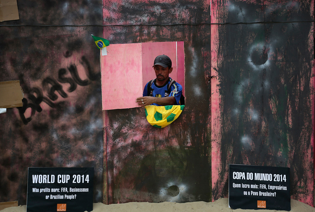 . A man looks out from an installation depicting a \'slum area\' which was set up as a form of protest on the Copacabana beach in Rio de Janeiro, Brazil, Tuesday, June 10, 2014. Organizers were protesting against the government\'s spending on the World Cup instead of services for the people of Brazil. The World Cup 2014 tournament will be held in Brazil and starts on June 12.(AP Photo/Wong Maye-E)