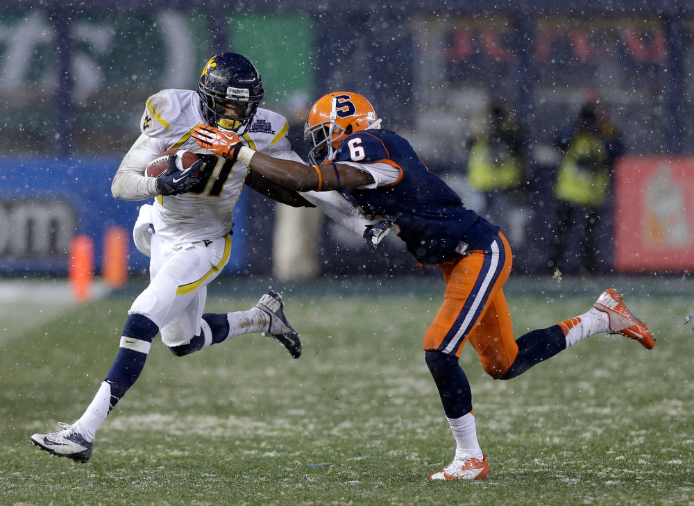 Description of . West Virginia wide receiver J.D. Woods (81) is stopped by Syracuse\'s Ritchy Desir (6) during the second half of the Pinstripe Bowl NCAA college football game at Yankee Stadium in New York, Saturday, Dec. 29, 2012. Syracuse won 38-14. (AP Photo/Kathy Willens)