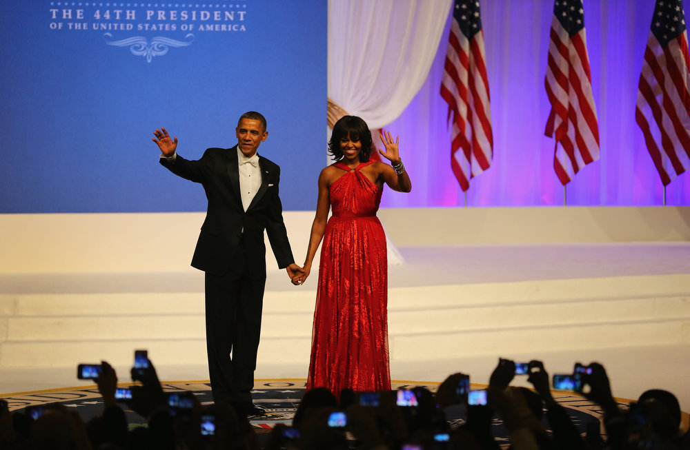 Description of . U.S. President Barack Obama and first lady Michelle Obama greet the crowd at the Commander-In-Chief's Inaugural Ball January 21, 2013 in Washington, DC. Obama was sworn in today for his second term in a public ceremonial swearing in.  (Photo by Joe Raedle/Getty Images)
