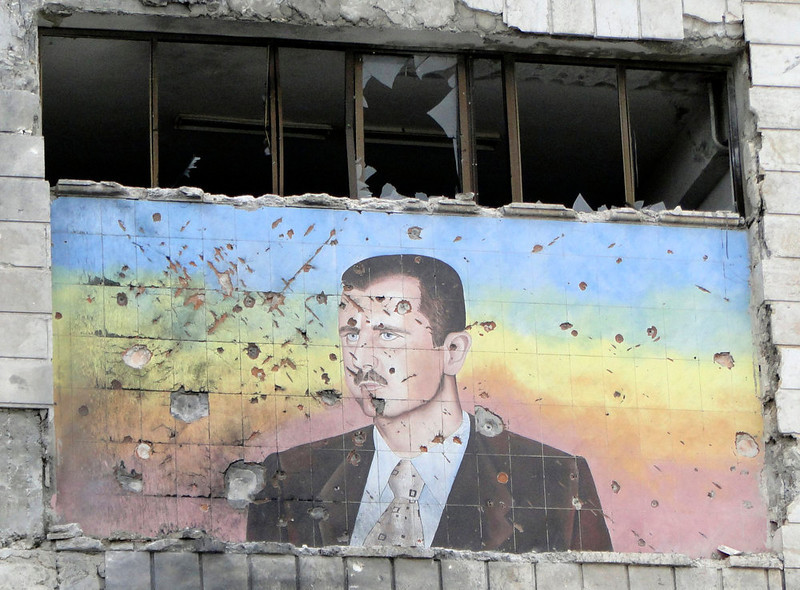 . A picture of Syria\'s President Bashar al-Assad riddled with holes is seen on the facade of the police academy in Aleppo, after it was captured by Free Syrian Army fighters, March 4, 2013. On Sunday rebels said they captured a police academy on the outskirt of Aleppo, after days of fighting in which rebels killed 150 soldiers, while sustaining heavy casualties. REUTERS/Mahmoud Hassano