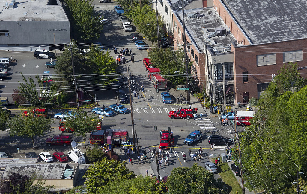 . In an aerial view, authorities and other emergency responders gather near Otto Miller Hall, upper left, at Seattle Pacific University on Thursday, June 5, 2014, in Seattle. Police say a university student on Thursday disarmed a lone gunman who entered a building and shot four people. A hospital spokeswoman says one man has died and three other people are injured, one critically. (AP Photo/The Seattle Times, Ellen M. Banner)