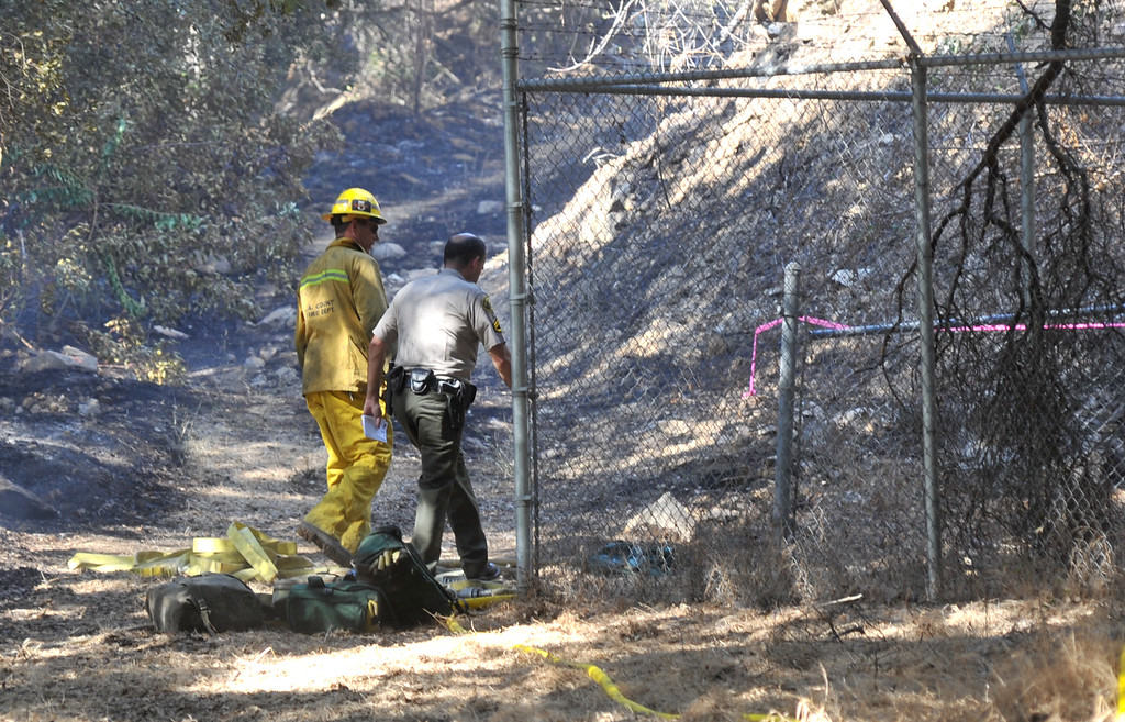 . A Los Angeles County fire investigator and a Sheriff\'s deputy examine an area that is possibly where the fire started that durned 6.9 acres in La Verne on Friday September 13, 2013.  (Whittier Daily News/Staff Photo by Keith Durflinger)