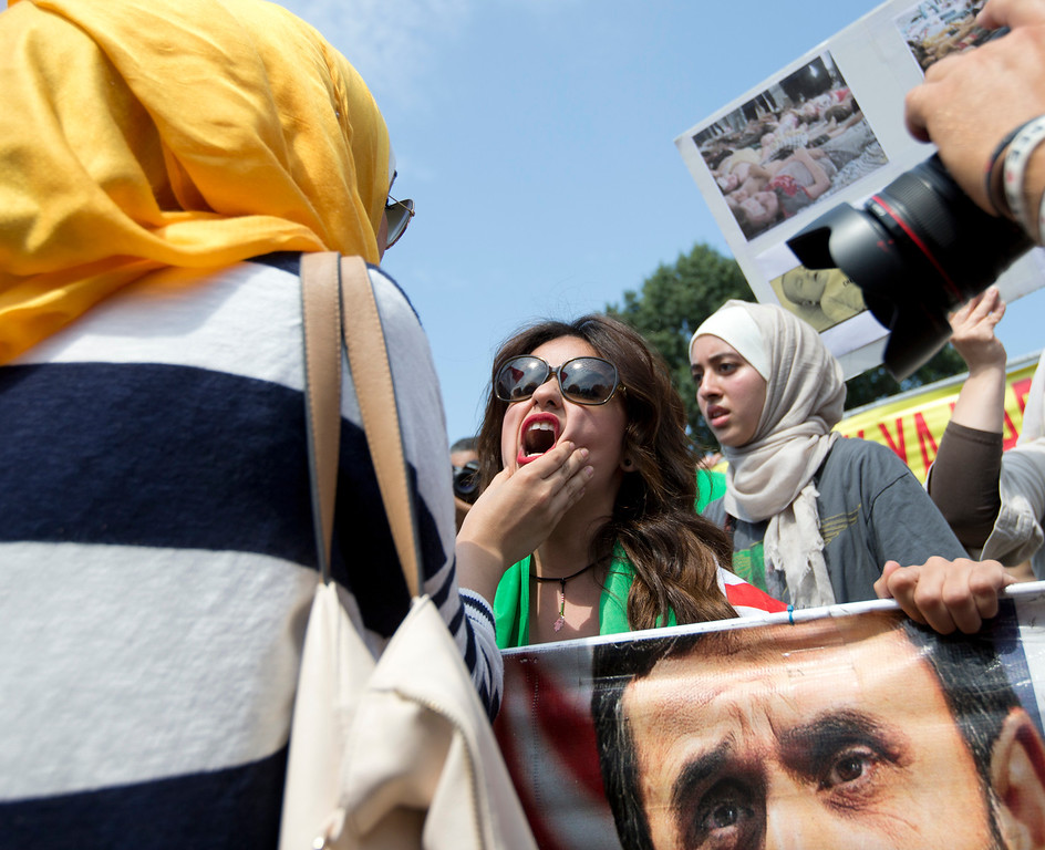 """. An unidentified Syrian protester, left, who opposes U.S. military action in Syria, grabs the face of Asmaa Al-Ghafari, a self-described \""""Syrian American revolutionist\"""", who favors U.S. action, as  protesters clash during multiple heated demonstrations in front of the White House in Washington, Saturday, Aug. 31, 2013. (AP Photo/Carolyn Kaster)"""