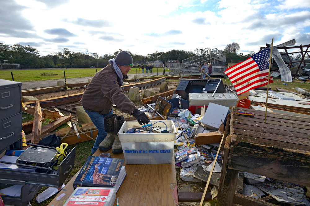Description of . Murphy High School teacher Leland Howard tries to salvage items where his algebra classroom once stood in a temporary building at Murphy High School, Wednesday, Dec. 26, 2012, as residents clean up and assess the damage from a Christmas Day tornado Wednesday, Dec. 26, 2012  in Mobile, Ala. With only a handful of injuries and no deaths reported statewide from the storms, the head of the state's emergency response said it was difficult to fathom how the toll wasn't worse. (AP Photo/G.M. Andrews)