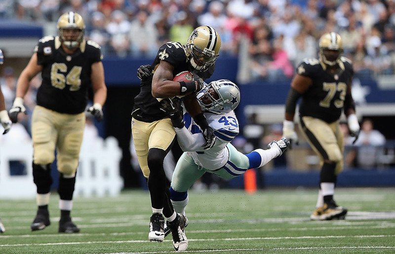 . Marques Colston #12 of the New Orleans Saints runs the ball past Gerald Sensabaugh #43 of the Dallas Cowboys at Cowboys Stadium on December 23, 2012 in Arlington, Texas.  (Photo by Ronald Martinez/Getty Images)
