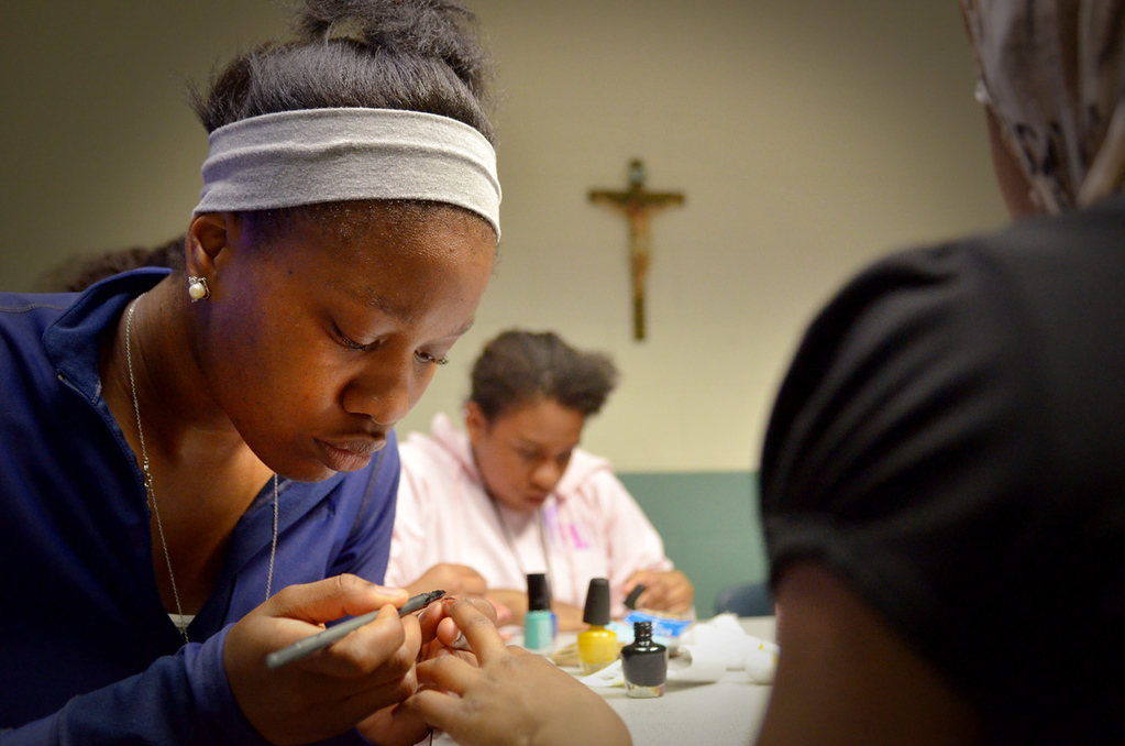 . Rika Shabazz  paints the fingernails of 11-year-old Saida Mkomo during a volunteer shift at Mary\'s Place, a transitional shelter in Minneapolis. (Pioneer Press: John Autey)