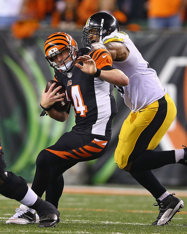 . Andy Dalton #14 of the Cincinnati Bengals runs with the ball dwhile defended by LaMarr Woodley #56 of the Pittsburgh Steelers during the game at Paul Brown Stadium on September 16, 2013 in Cincinnati, Ohio.  (Photo by Andy Lyons/Getty Images)
