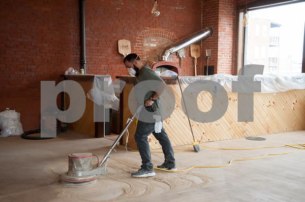 02/02/18 Wesley Bunnell | Staff David Ramirez of Ramon Ramirez Floors sands down the original flooring for Five Churches Brewery located at 193 Arch St. in New Britain in preparation of its opening. A brick pizza oven can be seen in the back corner.