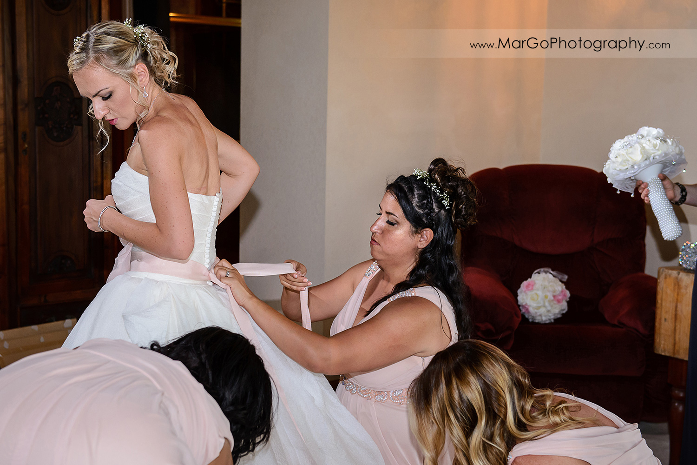 bridesmaids helping bride with wedding dress