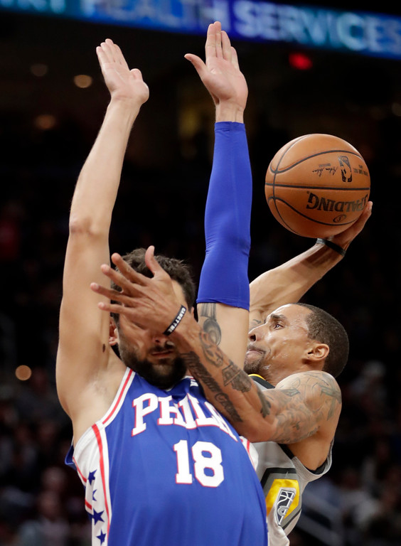 . Cleveland Cavaliers\' George Hill, right, drives to the basket against Philadelphia 76ers\' Marco Belinelli, from Italy, in the first half of an NBA basketball game, Thursday, March 1, 2018, in Cleveland. (AP Photo/Tony Dejak)