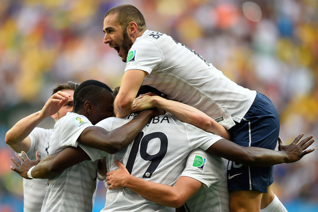 . France\'s midfielder Paul Pogba (C, hidden) celebrates with France\'s forward Karim Benzema (top) and other teammates after scoring the first goal during a Round of 16 football match between France and Nigeria at Mane Garrincha National Stadium in Brasilia during the 2014 FIFA World Cup on June 30, 2014.  FABRICE COFFRINI/AFP/Getty Images