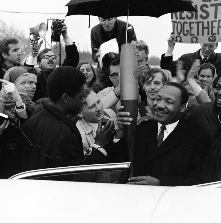 """. Dr. Martin Luther King holds a \""""peace torch\"""" during his speech addressed to a protest vigil of 400 persons outside the Santa Rita Prison Farm, California, Jan. 15, 1968. Dr. King visited folk singer Joan Baez, her mother and other draft protesters who are serving 45-day sentences, following their arrests before Christmas at the Oakland Induction Center. (AP Photo)"""