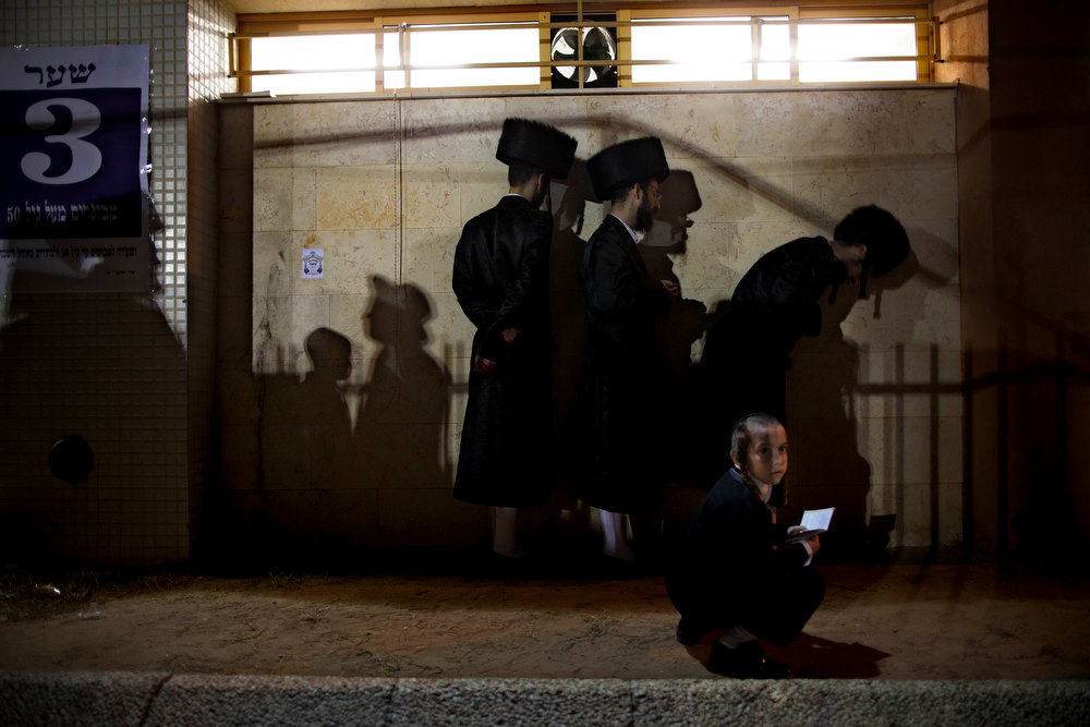 . Ultra-Orthodox Jews pray in the men\'s section during a traditional Jewish wedding ceremony of the great-grandson of the Rabbi of the Sanz Hasidic dynasty, in Netanya, Israel, Wednesday, Jan. 2, 2013. Thousands of people attended the wedding. (AP Photo/Oded Balilty)