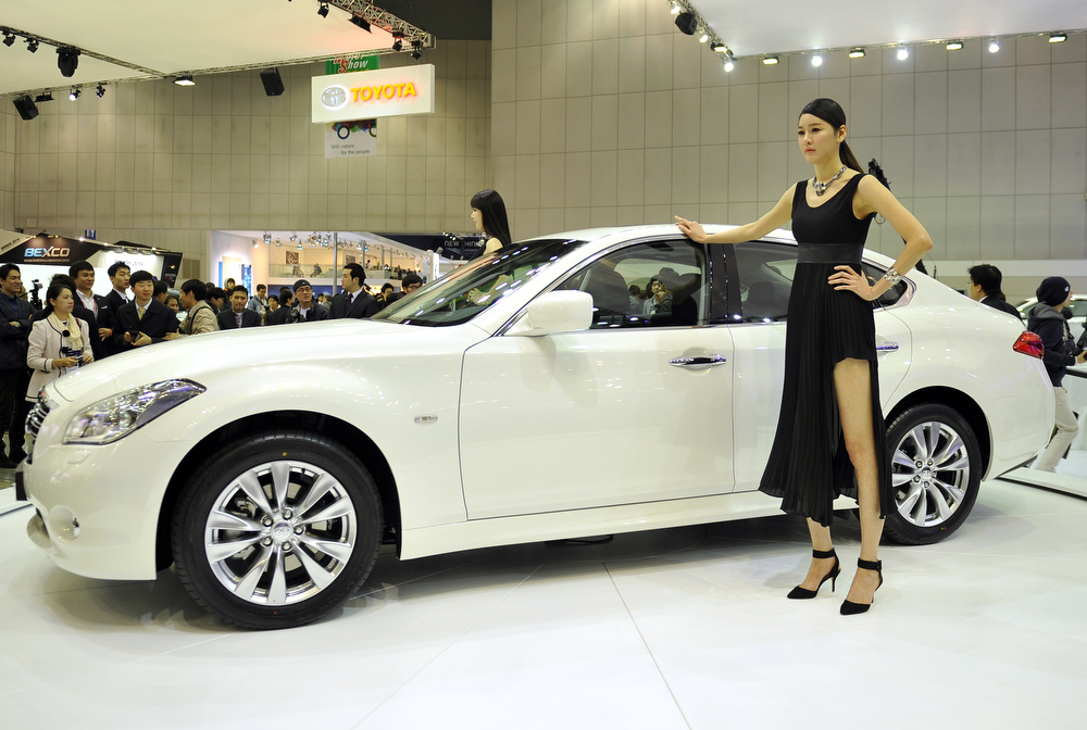 . South Korean models pose with Infiniti M30d during a press preview of the Seoul Motor Show in Goyang, north of Seoul, on March 28, 2013. South Korea\'s largest international auto show will open on March 29, with all Korean car manufacturers showing their latest cars and concepts amongst the 384 companies from 14 countries taking part in the event.  UNG YEON-JE/AFP/Getty Images