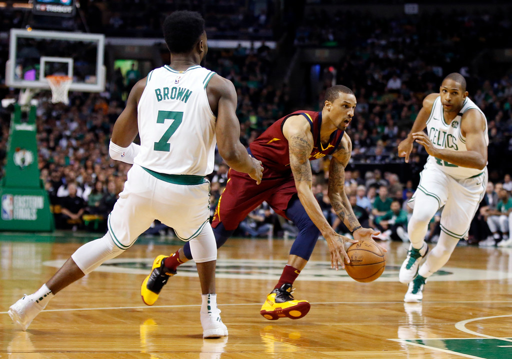 . Cleveland Cavaliers guard George Hill drives through the defense of Boston Celtics guard Jaylen Brown (7) and forward Al Horford during the first quarter of Game 1 of the NBA basketball Eastern Conference Finals, Sunday, May 13, 2018, in Boston. (AP Photo/Michael Dwyer)
