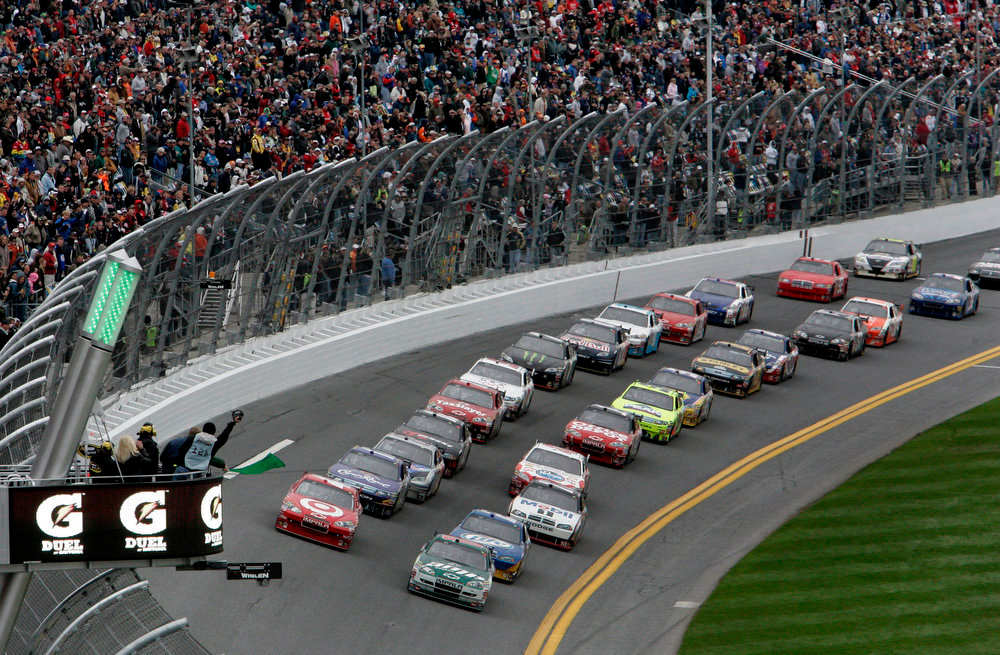 Description of . NASCAR driver\'s Juan Pablo Montoya, front left, of Colombia, and Dale Earnhardt Jr., front right, lead the field as they take the green flag to start the second of two Gatorade 150-mile qualifying auto races for the Daytona 500 at Daytona International Speedway in Daytona Beach, Fla. on Thursday, Feb. 11, 2010.(AP Photo/David Graham)