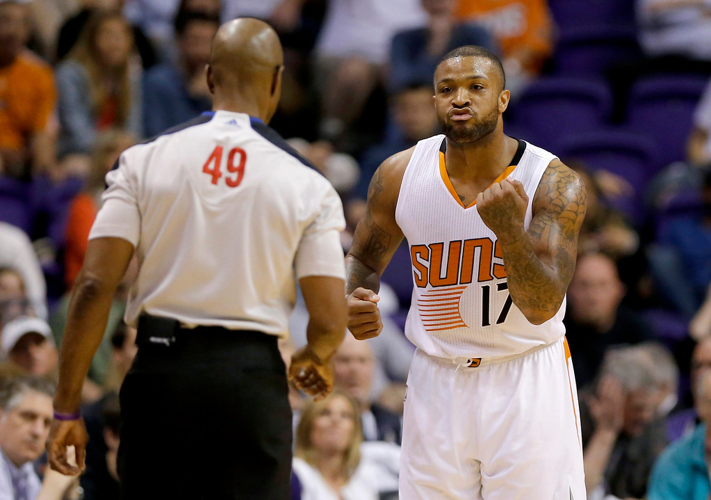 . Phoenix Suns forward P.J. Tucker (17) reacts to a foul called on him by referee Tom Washington (49) during the second half of an NBA basketball game against the Los Angeles Clippers, Wednesday, April 2, 2014,in Phoenix. The Clippers won 112-108. (AP Photo/Matt York)