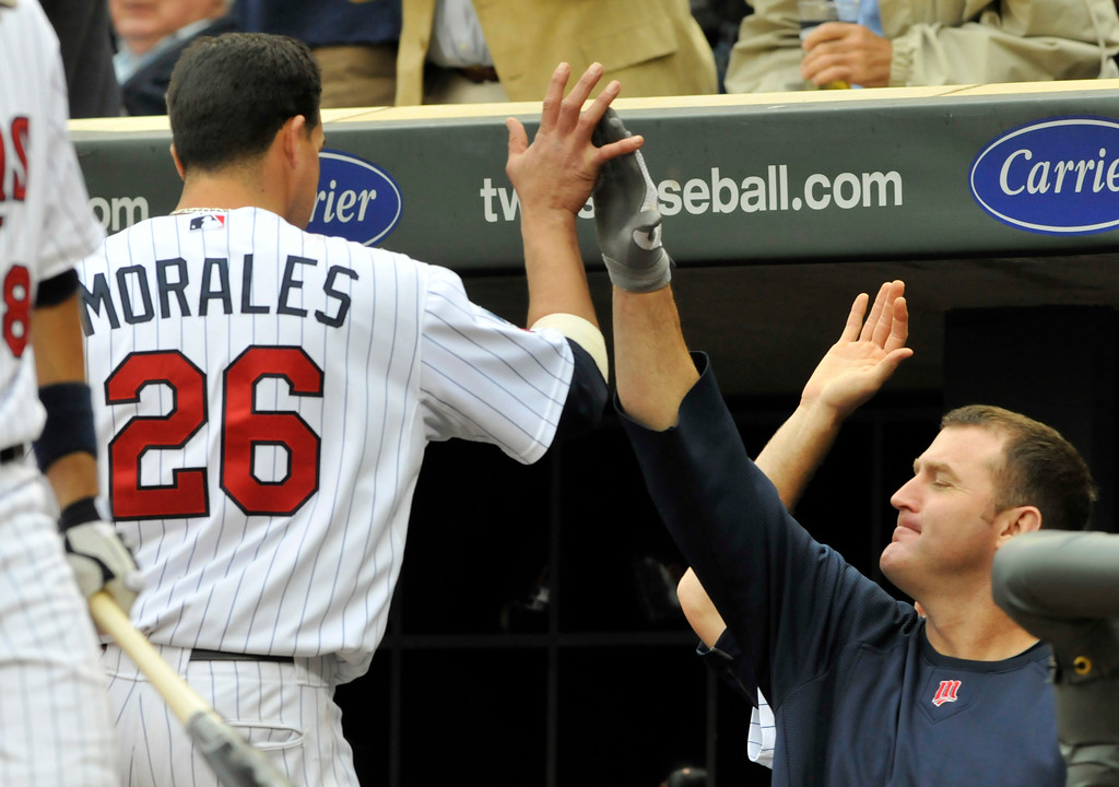 . Minnesota Twins\' Jim Thome, right, congratulates Jose Morales after he scored on a double by Matt Tolbert, against the Cleveland Indians in the sixth inning of a baseball game, Wednesday, Sept. 22, 2010, in Minneapolis. Morales had three RBI\'s in the Twins\' 5-1 win. (AP Photo/Jim Mone)