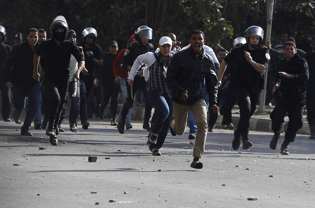 . Riot policemen run towards protesters opposing Egyptian President Mohamed Mursi during clashes along Qasr Al Nil bridge, which leads to Tahrir Square in Cairo March 9, 2013.  REUTERS/Amr Abdallah Dalsh