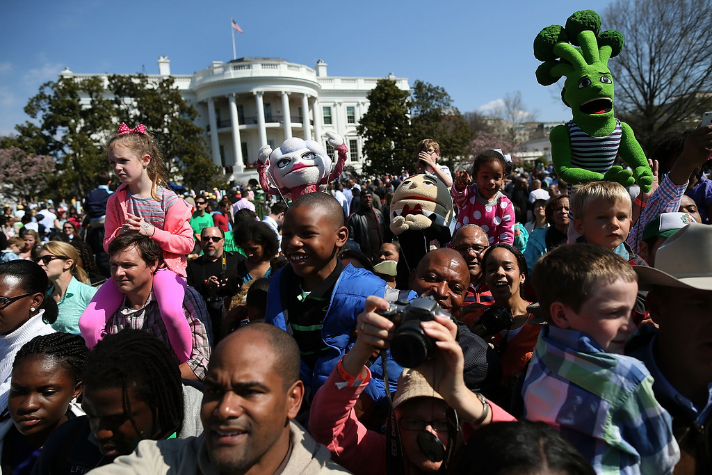 . People watch as U.S. President Barack Obama reads a book to children during the annual Easter Egg Roll on the White House tennis court April 1, 2013 in Washington, DC. Thousands of people are expected to attend the 134-year-old tradition of rolling colored eggs down the White House lawn that was started by President Rutherford B. Hayes in 1878.  (Photo by Mark Wilson/Getty Images)