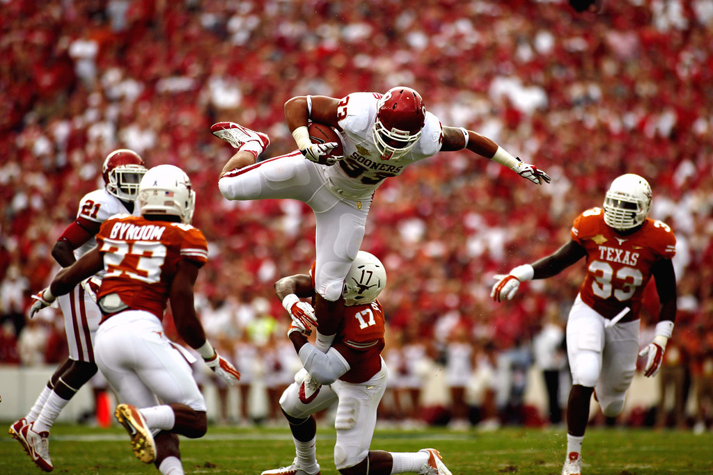 . Oklahoma\'s Trey Millard (33) is tackled by Texas\' Adrian Phillips (17) during the first half of an NCAA college football game at the Cotton Bowl Saturday, Oct. 12, 2013, in Dallas. (AP Photo/The Daily Texan, Chelsea Purgahn)
