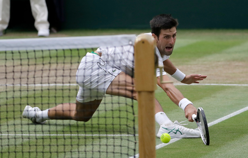 . Serbia\'s Novak Djokovic returns the ball to Rafael Nadal of Spain during their men\'s singles semifinals match at the Wimbledon Tennis Championships, in London, Saturday July 14, 2018.(AP Photo/Ben Curtis)
