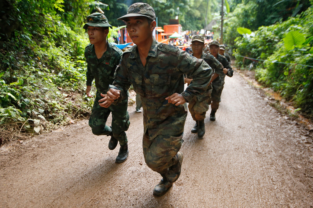 . Thai soldiers make their way up at the entrance to a cave complex where 12 boys and their soccer coach has been trapped, in Mae Sai, Chiang Rai province, in northern Thailand, Wednesday, July 4, 2018. The Thai soccer teammates stranded more than a week in the partly flooded cave said they were healthy on a video released Wednesday, as heavy rains forecast for later this week could complicate plans to safely extract them. (AP Photo/Sakchai Lalit)
