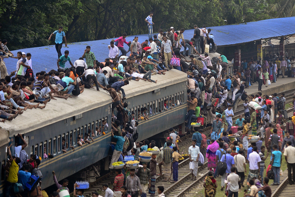. Bangladeshi commuters board a train as they rush home to be with their families in remote villages, ahead of the Muslim festival of Eid al-Adha, in Dhaka on October 3, 2014. Muslims across the world are preparing to celebrate the annual festival of Eid al-Adha, or the Festival of Sacrifice, which marks the end of the Hajj pilgrimage to Mecca and in commemoration of Prophet Abraham\'s readiness to sacrifice his son to show obedience to God. MUNIR UZ ZAMAN/AFP/Getty Images
