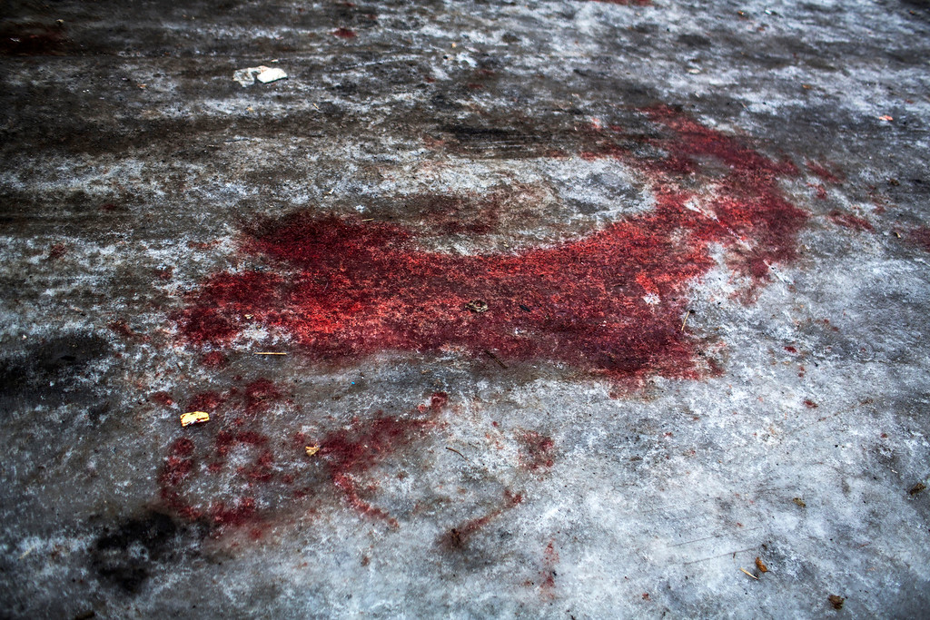 . Blood from a DNR soldier killed at the airport is seen at the gate of the morgue of Kalinisky Hospital, center of Donetsk, Ukraine. Sunday, Jan. 18, 2015. The separatist stronghold, Donetsk, was shaken by intense outgoing and incoming artillery fire as a bitter battle raged for control over the city\'s airport. Streets in the city, which was home to 1 million people before unrest erupted in spring, were completely deserted and the windows of apartments in the center rattled from incessant rocket and mortar fire. (AP Photo/Manu Brabo)
