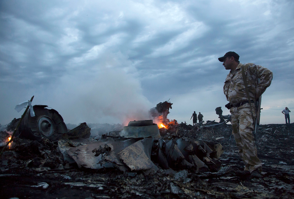 . People walk amongst the debris, at the crash site of a passenger plane near the village of Grabovo, Ukraine, Thursday, July 17, 2014.  A Ukrainian official said a passenger plane carrying 295 people was shot down as it flew over the country and plumes of black smoke rose up near a rebel-held village in eastern Ukraine. Malaysia Airlines tweeted that it lost contact with one of its flights as it was traveling from Amsterdam to Kuala Lumpur over Ukrainian airspace.  (AP Photo/Dmitry Lovetsky, File)